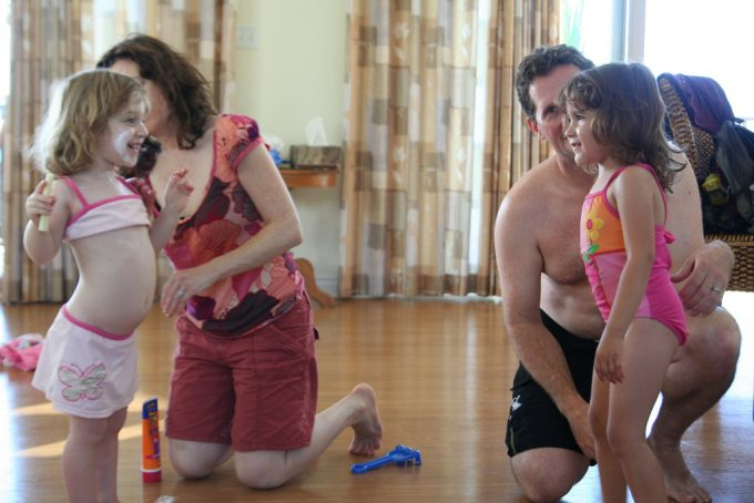 parents putting sunscreen on children