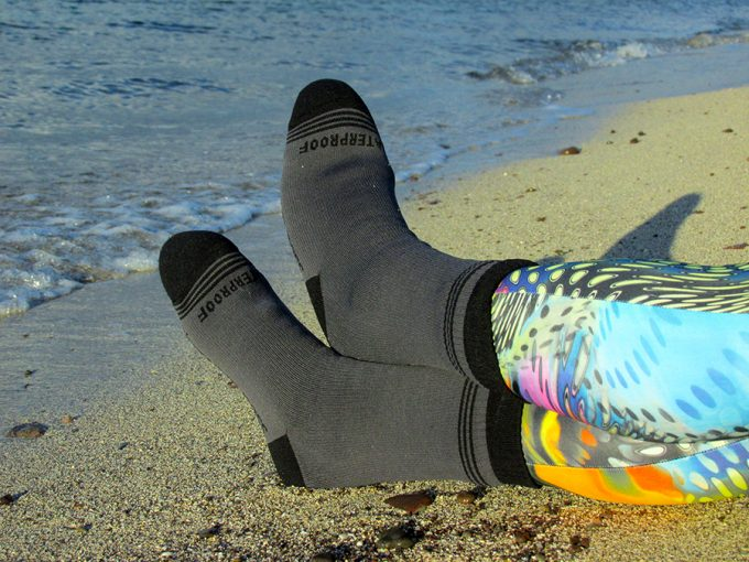 laying on beach sand with waterproof socks