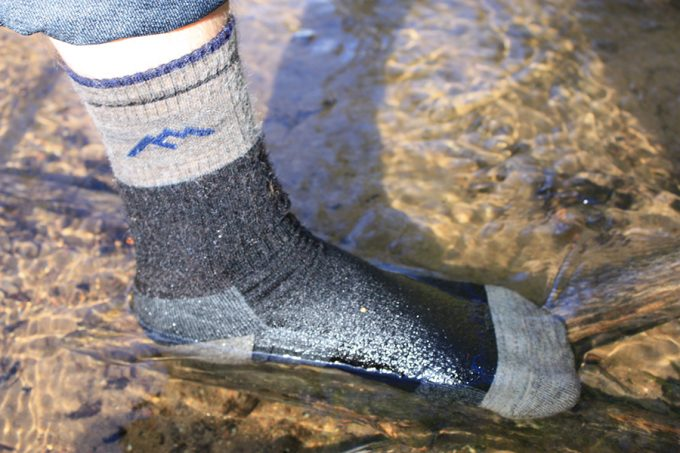 stepping into pond with waterproof socks