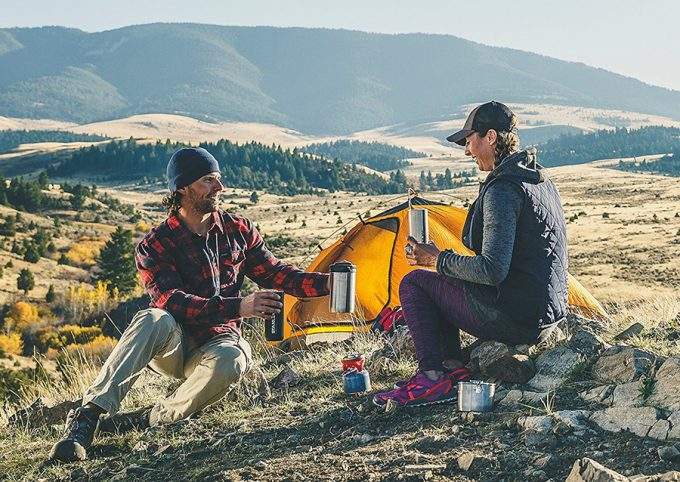 couple drinking hot coffee on camp