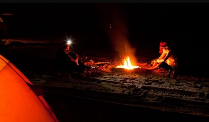 sitting by the fire with headlamps