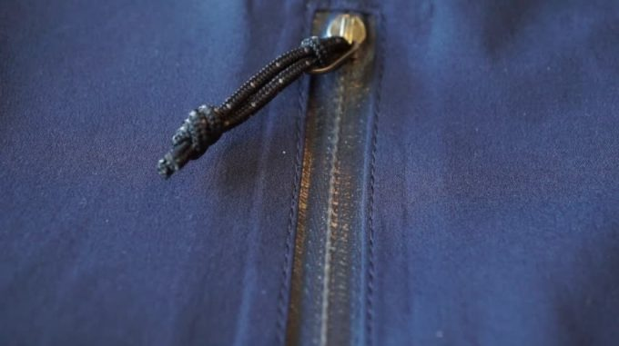 large rain drops falling on dark blue waterproof weatherproof membrane clothes