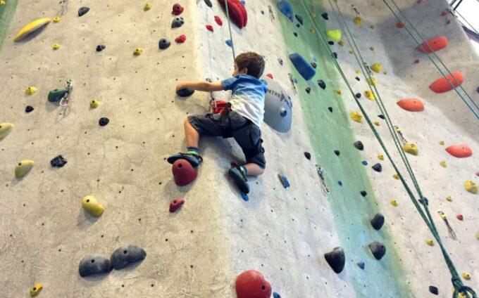 kid learning to rock climb