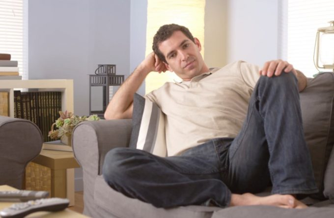 man resting on couch at home